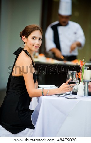 An attractive well-dressed woman having a formal meal outdoors - stock photo