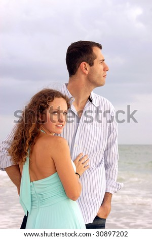 An attractive well dressed young couple  with their bodies facing each other, the man is looking out to the ocean in profile. The woman is turned and looking at viewer - stock photo