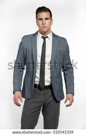 An attractive white male wearing a fitted gray suit with a white shirt, skinny tie, gray pants and a black belt in a studio setting on a white background posing and looking at the camera. - stock photo