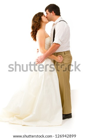 An attractive woman and her handsome husband wear their wedding attire in the studio agains an isolated white background. - stock photo