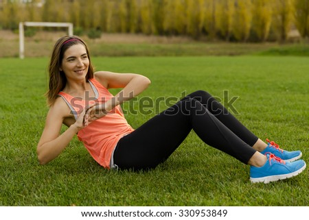 An attractive woman exercising outdoor on a soccer field - stock photo