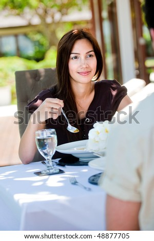 An attractive woman having a meal outdoors with her partner - stock photo