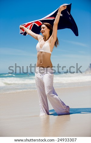 An attractive woman holding an Aussie beach towel - stock photo