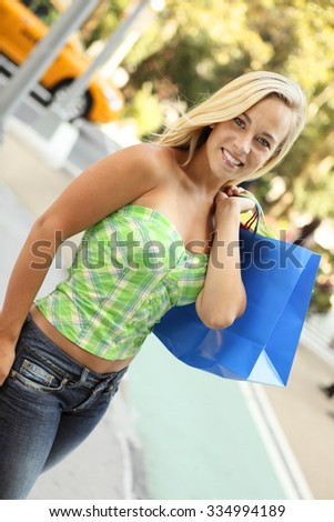 An attractive woman holds bags over shoulder while smiling at viewer.