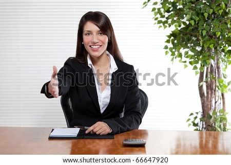An attractive woman in a business suit extends her hand for a friendly handshake