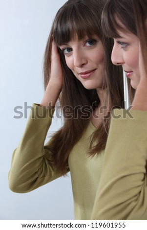 An attractive woman looking at her reflection in the mirror - stock photo