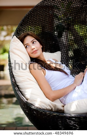 An attractive woman lounging and relaxing on a luxurious chair outdoors - stock photo