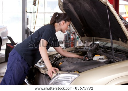 An attractive woman mechanic working on a car in a repair shop - stock photo