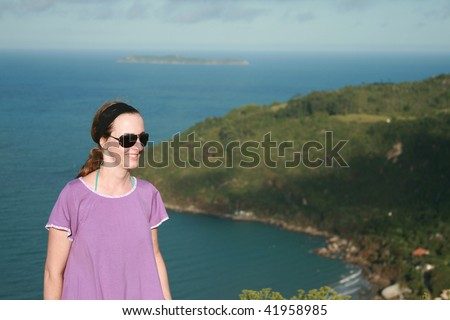 An attractive woman on the top of a big mountain enjoying the view. - stock photo