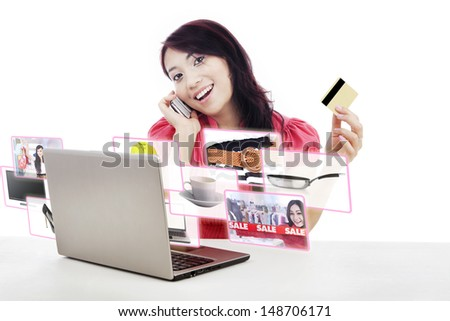 An attractive woman purchasing product online using her laptop computer, credit card, and mobile phone,  - stock photo