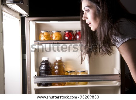 An attractive woman raids the refrigerator late at night looking for a food snack - stock photo