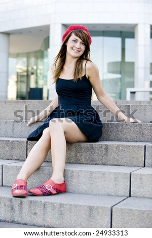 An attractive woman sitting down in the city - stock photo
