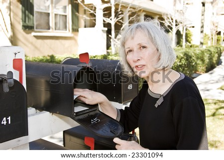 An attractive woman talking to her neighbor while she checks her mailbox - stock photo