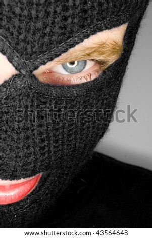an attractive woman wearing a balaclava. - stock photo
