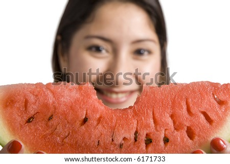 An attractive woman with a bitten slice of watermelon