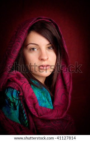 An attractive woman with a red pattern scarf over her head.