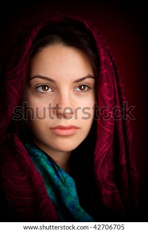 An attractive woman with a red pattern scarf over her head. - stock photo