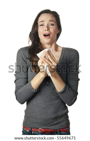 An attractive woman with hay fever or a cold sneezing into tissue - stock photo