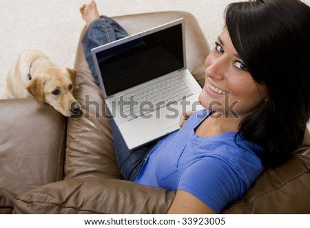 An attractive woman works on her laptop with her puppy at her side