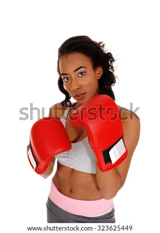An attractive young african american girl in sports wear, wearing red boxing