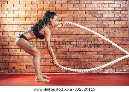 An attractive young and athletic girl using training ropes in a gym. on the background wall of red brick. - stock photo