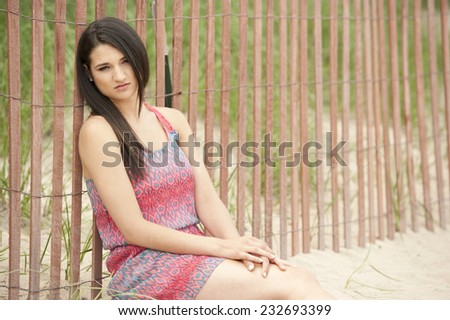 An attractive young and beautiful female model sitting at the beach on a sunny day. - stock photo