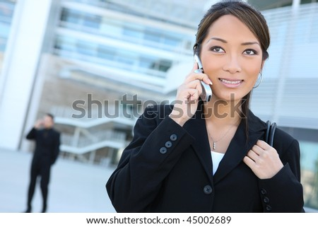 An attractive young asian business woman on the phone outside office building