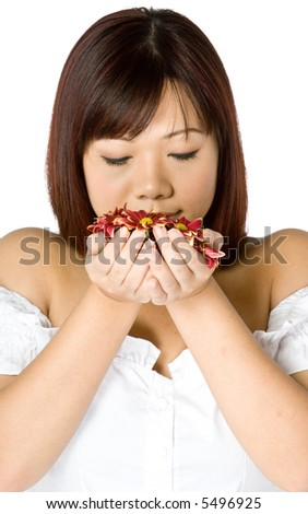 An attractive young Asian woman in white top holding red flowers on white background