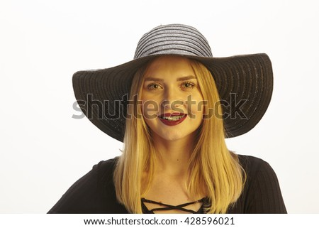 An attractive young blond woman wears a black blouse and black hat  and enjoys the sunset with warm colors.