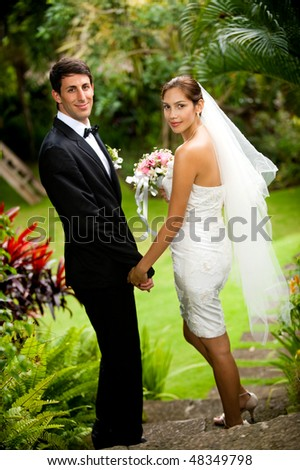 An attractive young bride and groom holding hands and walking down steps outdoors - stock photo
