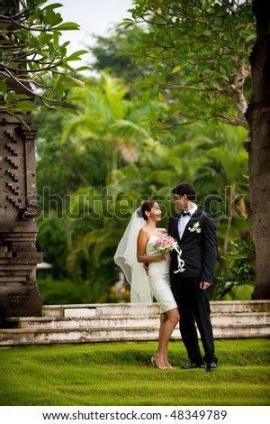 An attractive young bride and groom smiling at each other in a garden outdoors - stock photo