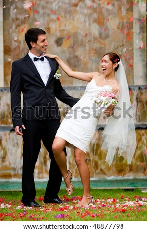 An attractive young bride and groom standing at a waterfall outdoors - stock photo