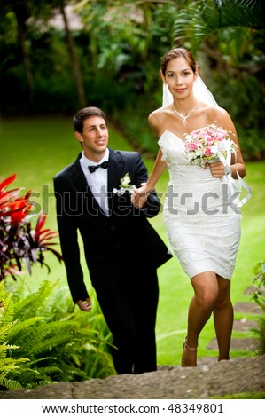 An attractive young bride leading her groom up some stone steps outdoors