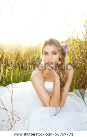 An attractive young bride wearing a white wedding dress and pearls is sitting with her head on her hand in the grass. Vertical shot. - stock photo