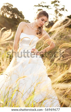 An attractive young bride wearing a white wedding dress and pearls is standing with her hand on her hip in a rural landscape. Vertical shot. - stock photo