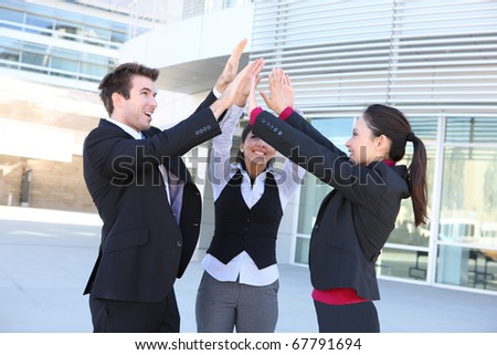 An attractive young business man and woman team celebrating at office building - stock photo