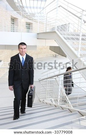 An attractive, young business man on stairs at office building - stock photo