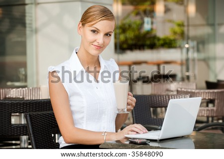 An attractive young businesswoman having a coffee while using a laptop
