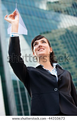 An attractive young businesswoman holding a paper plane against city backdrop - stock photo