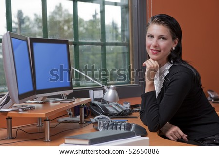 An attractive young businesswoman is sitting in front of a computer and smiling.  She is resting her chin on her hand. Horizontal shot. - stock photo