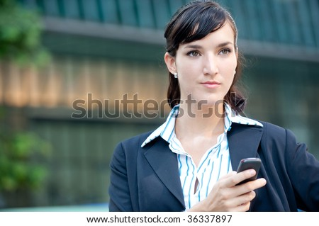 An attractive young businesswoman using her phone in the city