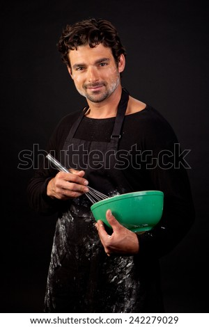 An attractive young caucasian man with dark features dressed as a baker with flour on his apron and face - stock photo