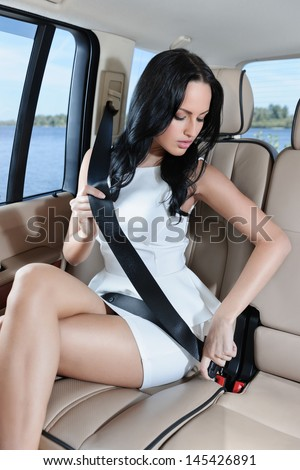 An attractive young Caucasian woman in a white dress fastening her seat belt before the car trip - stock photo