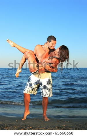 An attractive Young Couple enjoying a Romantic Getaway on the beach - stock photo
