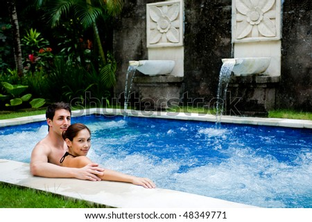 An attractive young couple in a jacuzzi pool outdoors - stock photo