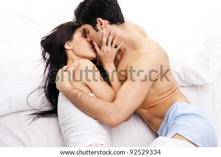 An attractive young couple in a loving embrace kissing one another in bed. - stock photo