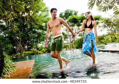 An attractive young couple in swimwear walking by a pool outdoors - stock photo