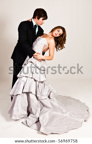 An attractive young couple in the midst of a dance move are dressed in formal attire. Vertical shot. - stock photo
