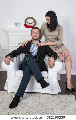 An attractive young couple. Maybe business style or a couple in love. A man sits on a chair beautiful girl embraces him. - stock photo