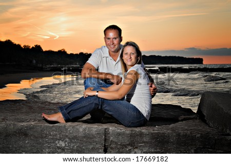 An attractive young couple posing on the beach at sunset.